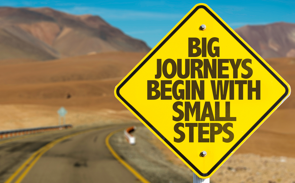 Big Journeys Begin With Small Steps sign on desert road-1