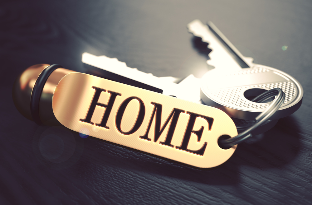 Keys and Golden Keyring with the Word Home over Black Wooden Table with Blur Effect. Toned Image.-1